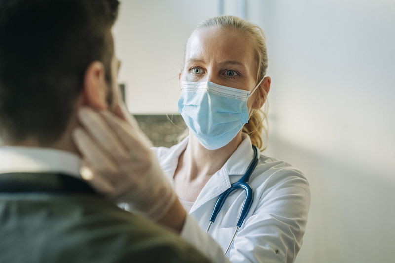 A doctor in a mask performs an exam.
