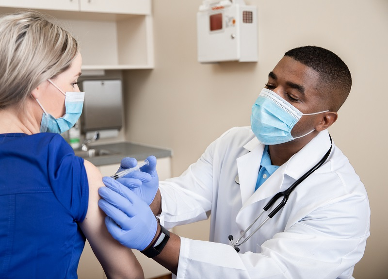 doctor giving healthcare worker the COVID-19 vaccine