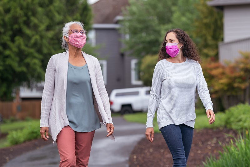 two women walking together while wearing face masks