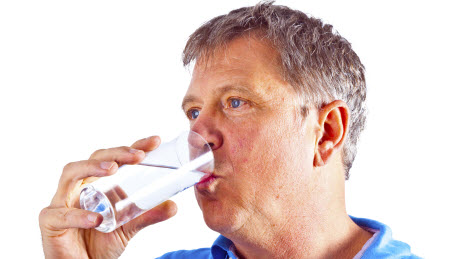 Man drinking water out of a glass.