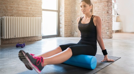 Woman using a foam roller in the gym.