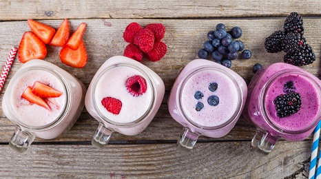 row of four mason jars with smoothies and fresh berries