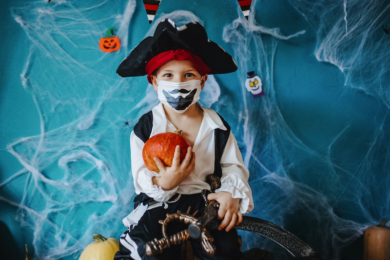 A young boy shows off his pirate Halloween costume and matching mask.