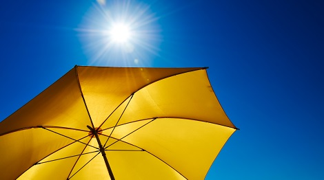 Using an umbrella to block the sun.