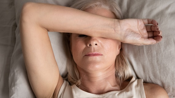 tired woman lying in bed touching her forehead