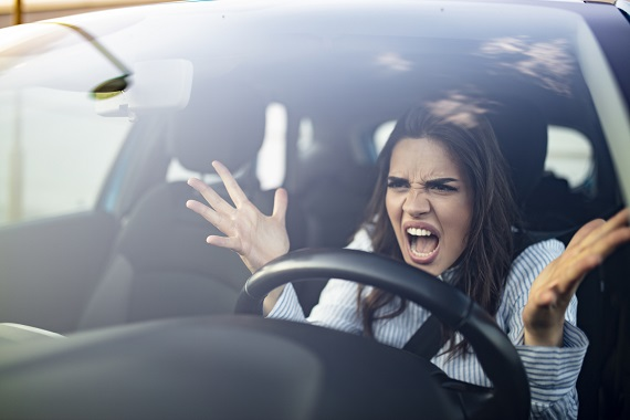 woman sitting in a car and raising her hands in anger