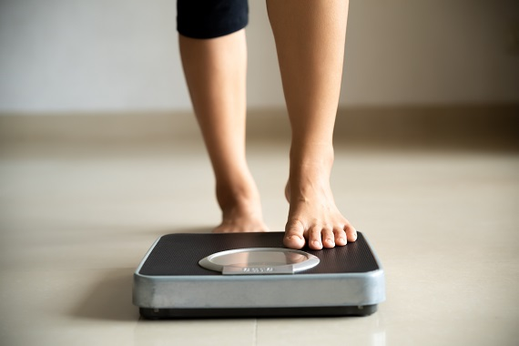 woman stepping one foot onto a scale