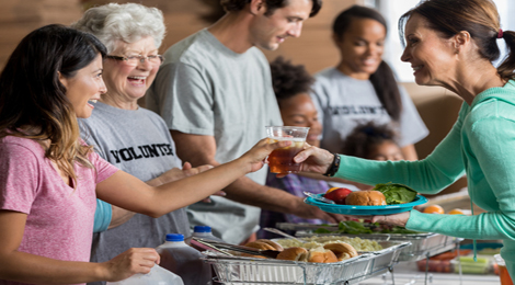 A volunteer handing out a Thanksgiving dinner for charity.