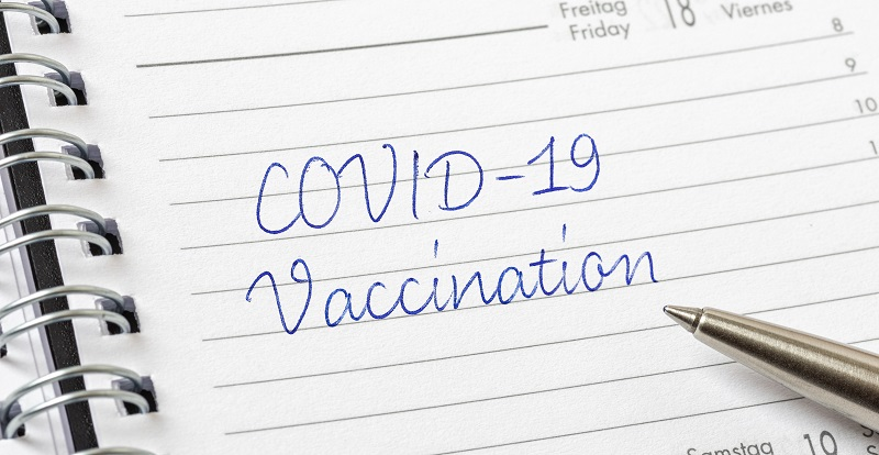 image of planner with COVID-19 vaccination written in it
