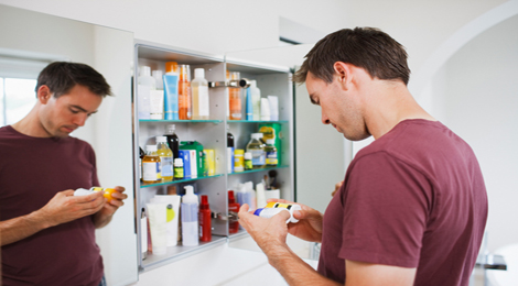Man looking through his medicine cabinet.