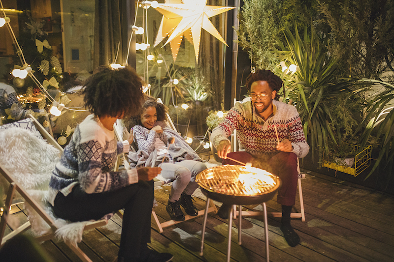 A family roasts marshmallows outside as they celebrate the holidays.