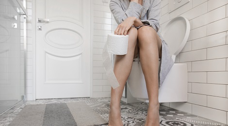 Patient with constipation sitting on toilet.