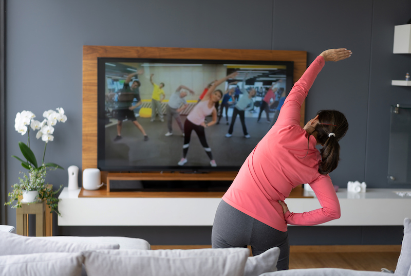 A woman works out with an online fitness class.