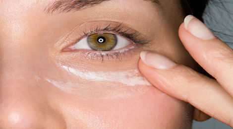 Using eye cream on your face.
