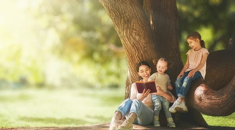 Family sitting and reading a book next to a tree.