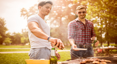 Two guys grilling in a park
