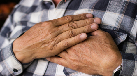 Hands holding chest because of heart pain.