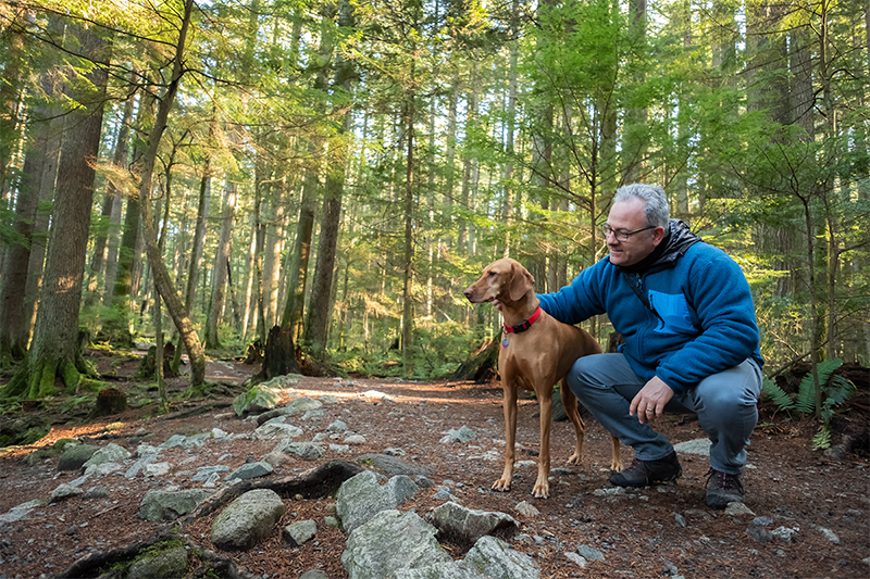 Man and dog hiking in the woods