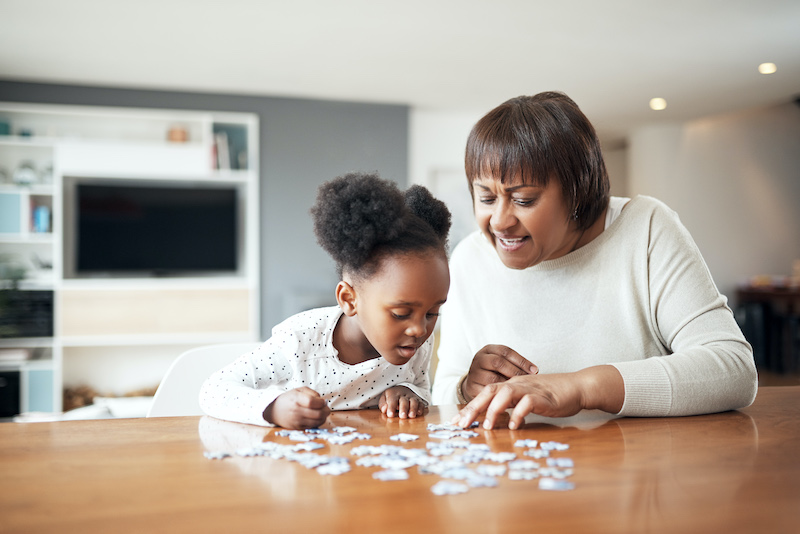 A little girl and her grandmother complete a jigsaw puzzle at home.