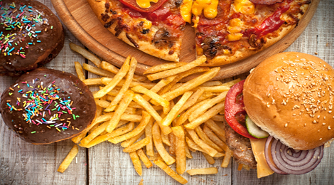 Burgers, fries, cupcakes, and pizza on a table.