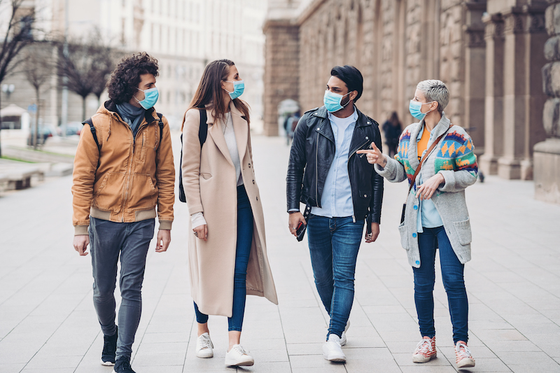 Four friends wear masks as they stroll down the street together.