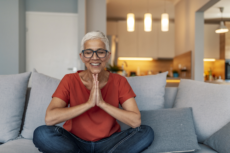 A woman meditates indoors on her couch.