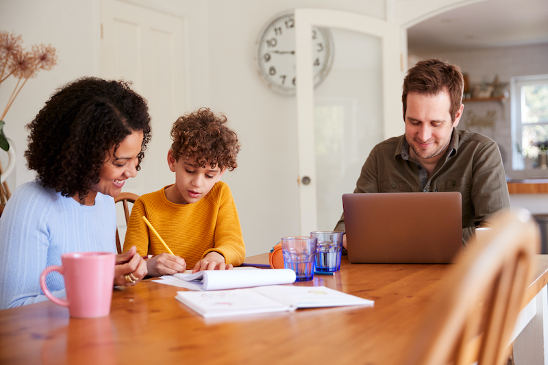 Two parents help their child with schoolwork at home.