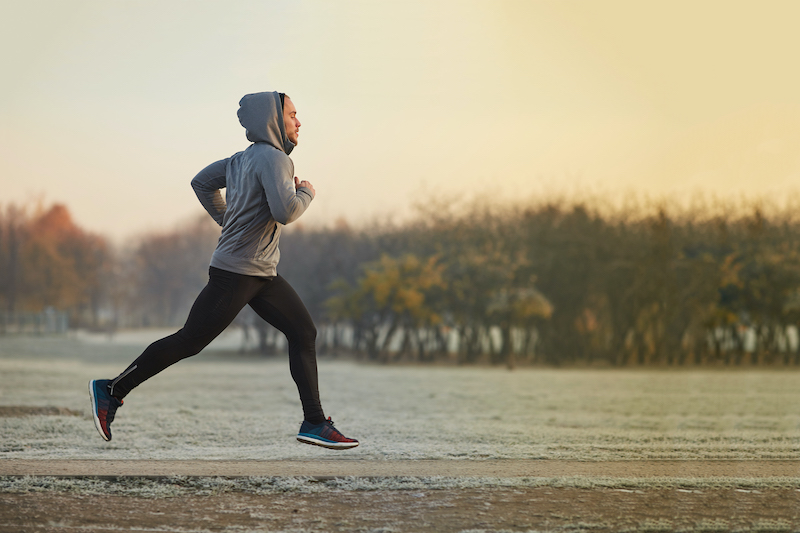 A man jogs outdoors in colder weather.