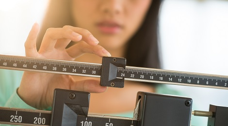 Women checking her weight on a scale.