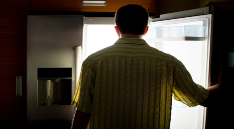 A man staring at his refrigerator in the middle of the night.
