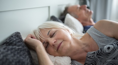 Elderly couple sleeping in bed at home.
