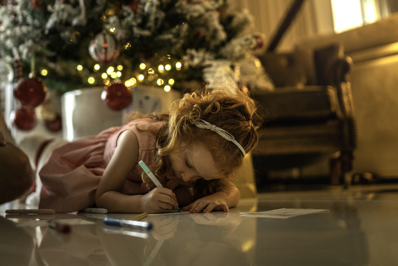 A young girl writes holiday cards in her home.
