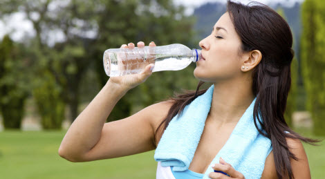 Woman drinking electrolytes after a work out.